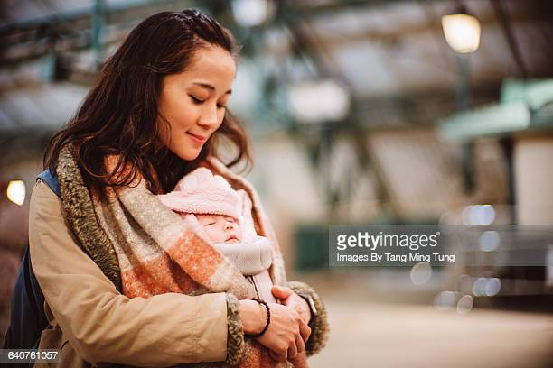 Mom carrying sleeping baby with carrier joyfully