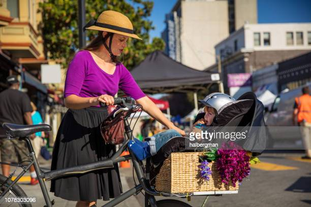 Mom Checking on Toddler Strapped Into Cargo Bike at Farmer's Market