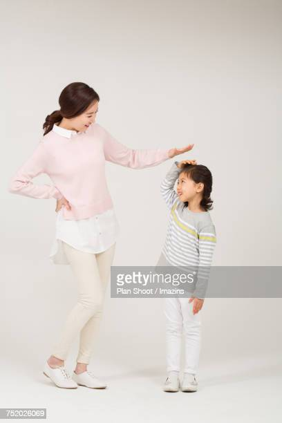 Mom checking the height of her daughter