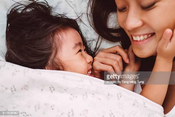 Mom & child playing joyfully on bed