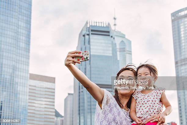 Mom & child taking selfies in downtown