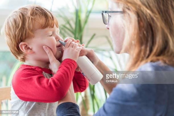 Mam reinigt Baby's neus met Blower en zoutoplossing neusspray