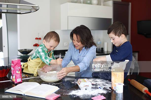 A mom cooking with her 2 boys