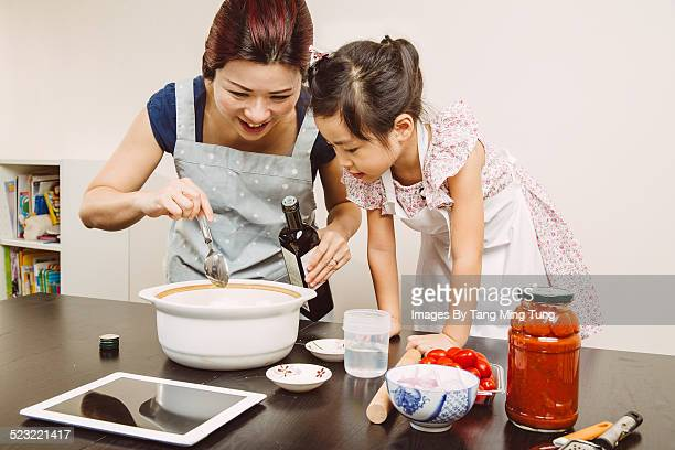 Mom cooking with toddler girl joyfully at home