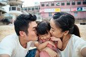 Mom & dad kissing lovely toddler girl's cheek
