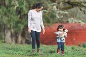 ethnic mom walks outside farm with