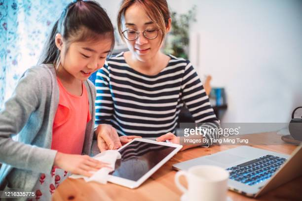 mom & daughter cleaning the surface of a digital tablet with disinfectant wipe at home - antiseptic wipe stock pictures, royalty-free photos & images