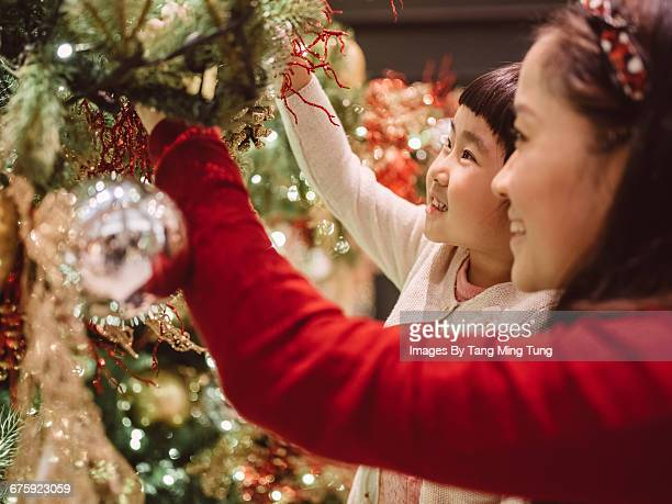 Mom & daughter decorating Christmas Tree