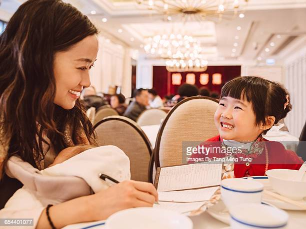 Mom & daughter having meal in Chinese restaurant