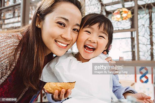 Mom & daughter having meal joyfully in restaurant