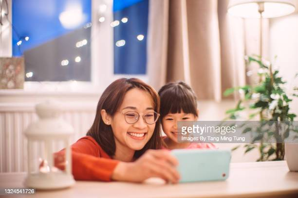 mom & daughter having video call joyfully on smartphone at home - flatten the curve stock pictures, royalty-free photos & images