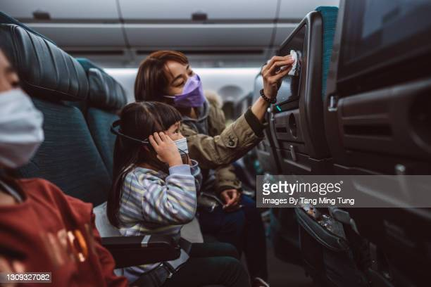 mom & daughter in protective face masks cleaning the seat-back tv screen with disinfectant surface wipe while travelling on the airplane - kid in airport stock pictures, royalty-free photos & images