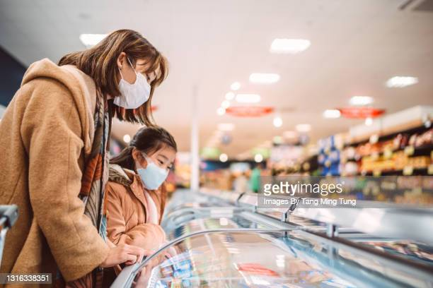 mom & daughter in protective face masks doing grocery shopping for organic frozen food in supermarket - flatten the curve stock pictures, royalty-free photos & images