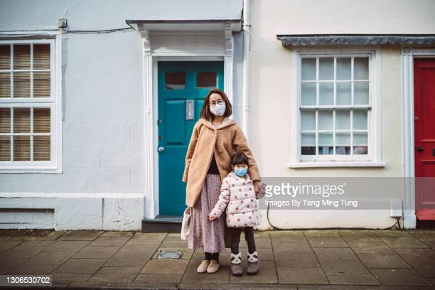 mom & daughter in protective face masks smiling joyfully at the camera against a town house while strolling on the street - standing stock pictures, royalty-free photos & images