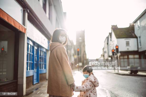 mom & daughter in protective face masks smiling joyfully at the camera while strolling along the street with closed shops in town in the morning - flatten the curve stock pictures, royalty-free photos & images