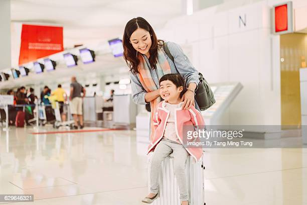 Mom & daughter playing joyfully in airport