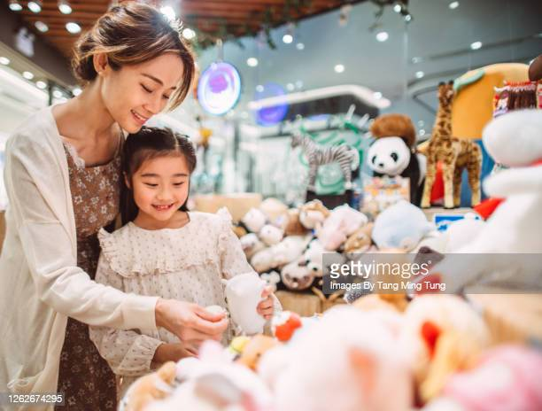 mom & daughter shopping for kid toys joyfully in a toy shop - ギフトショップ ストックフォトと画像