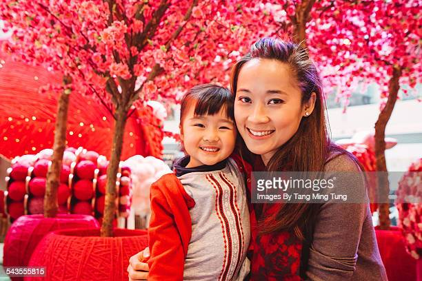 Mom & daughter smiling joyfully at camera
