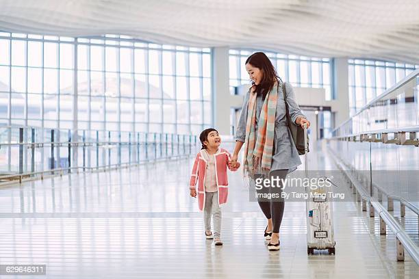 Mom & daughter strolling joyfully at airport