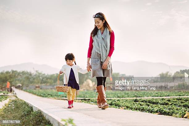 Mom & daughter strolling joyfully in the farm