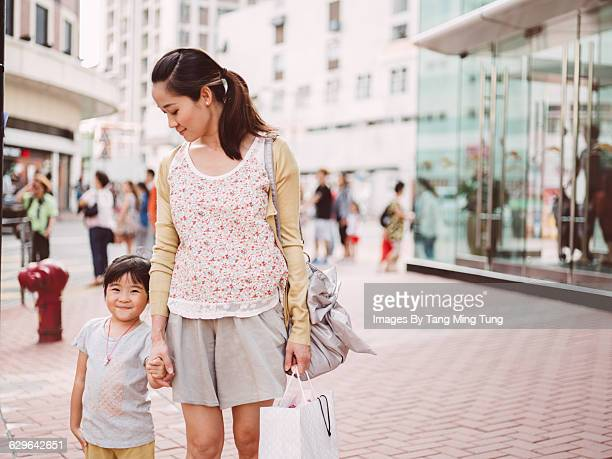 Mom & daughter strolling joyfully on street