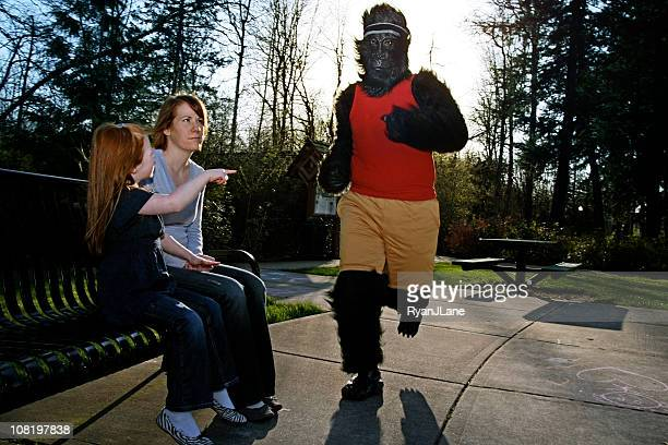 mom & daughter surprised by jogging gorilla - monkey suit stock pictures, royalty-free photos & images