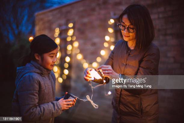 mom & daughter untangling the string lights together while they are decorating the garden at dusk - hanging stock pictures, royalty-free photos & images