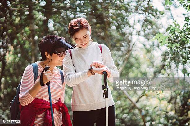 Mom & daughter using smartwatch while hiking