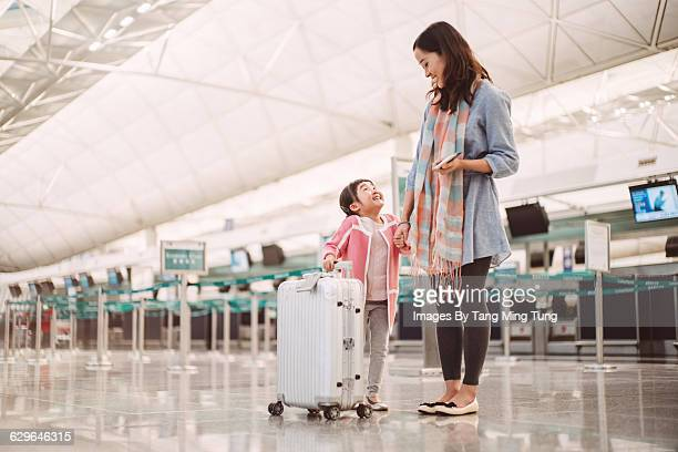 Mom & daughter waiting at check in counters