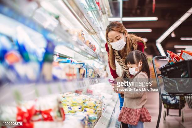 mom & daughter with surgical masks doing grocery shopping for diary products in supermarket - merchandise stock pictures, royalty-free photos & images