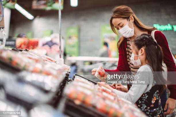 mom & daughter with surgical masks doing grocery shopping for fresh fruits in supermarket - choosing stock pictures, royalty-free photos & images
