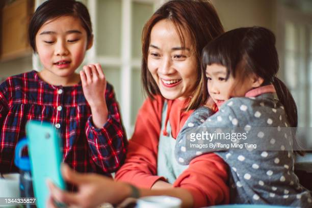 mom & daughters having video call joyfully on smartphone at home - mid adult men stock pictures, royalty-free photos & images