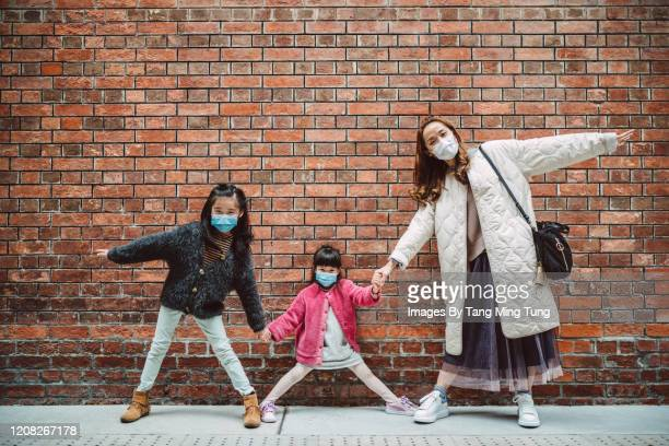 mom & daughters in medical face masks taking picture in front of brick wall - side by side stock pictures, royalty-free photos & images