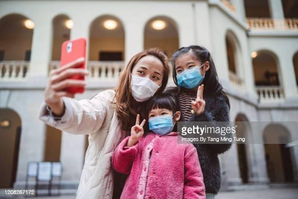 mom & daughters in medical face masks taking selfies joyfully in city - china coronavirus stockfoto's en -beelden