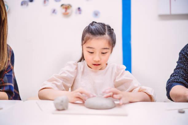 Mom & daughters making clay sculptures in workshop joyfully