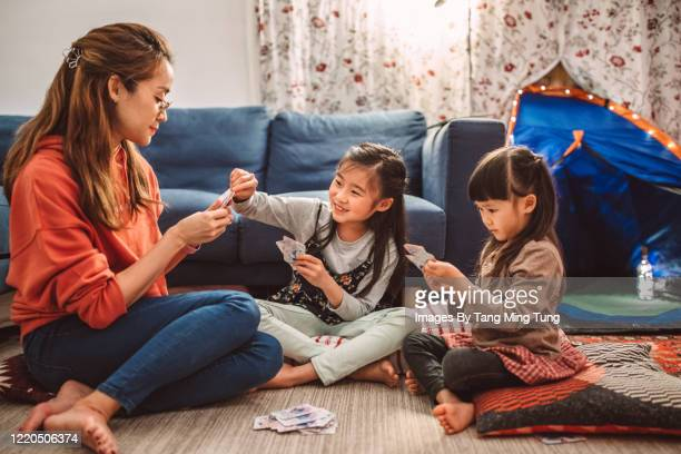 mom & daughters playing card games joyfully at home with a campfire & camping tent setting besides them in the evening.. - family stock pictures, royalty-free photos & images