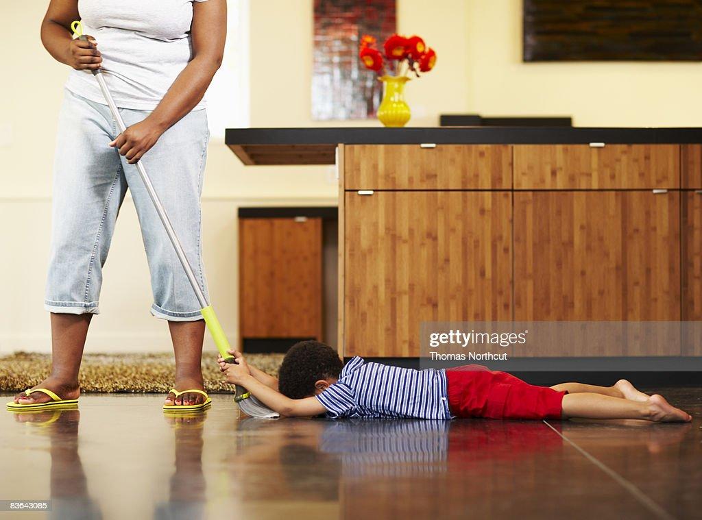 mom dragging boy across floor with broom : Stock Photo