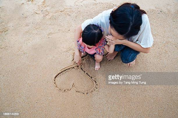 Mom drawing a heart in the sand with toddler girl