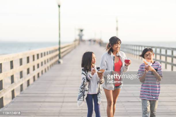 mom eating ice cream with her kids on a beach boardwalk - boardwalk stock pictures, royalty-free photos & images