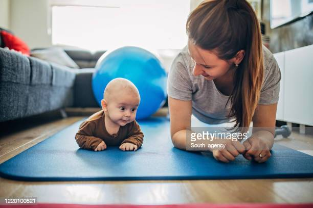 mama trainiert mit ihrem kleinen sohn zu hause - turner syndrome stock-fotos und bilder