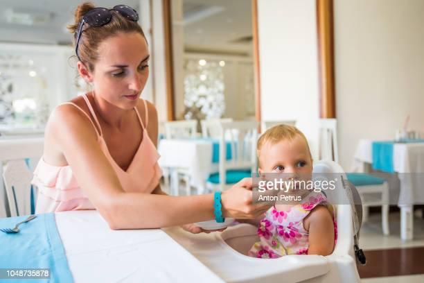 Mom feeding a one-year-old girl in a restaurant