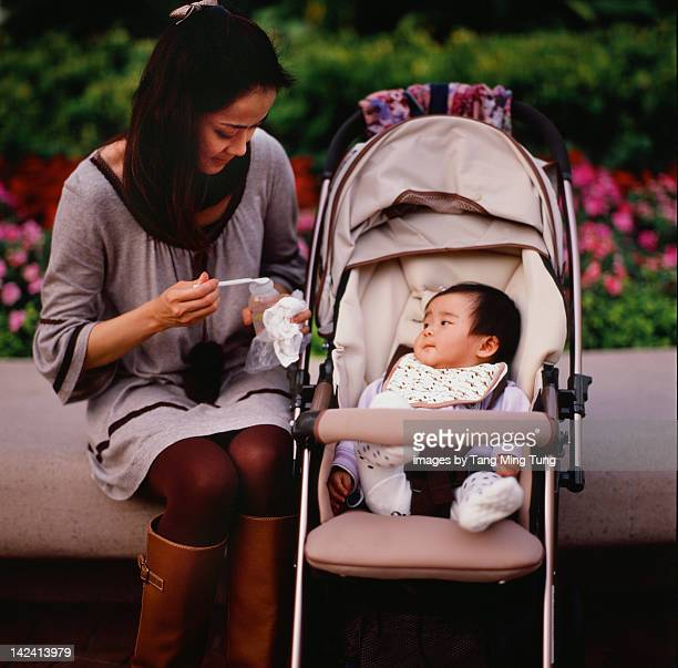 Mom feeding baby in park
