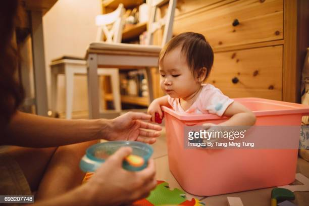 Mom feeding baby meal at home on the floor