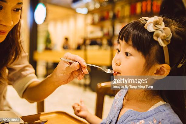 mom feeding dessert to daughter in cafe - beautiful chinese girls stock photos and pictures