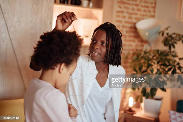 Mom fixing daughter's hair