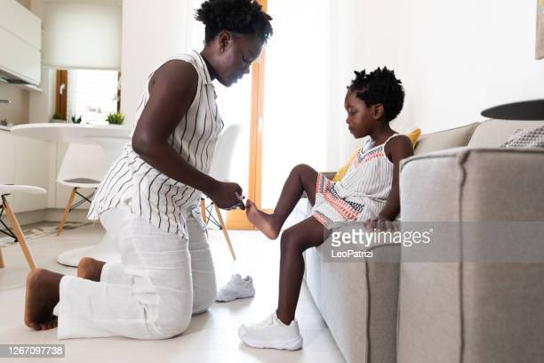 mom gets daughter ready for school in the morning - black shoe stock pictures, royalty-free photos & images