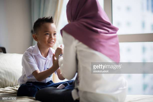mom getting her son ready for school - malay hijab stock photos and pictures