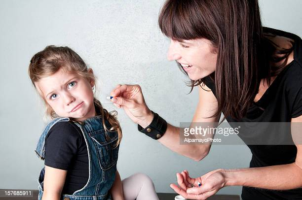 Mom giving medicine to little girl (rejecting it) - II