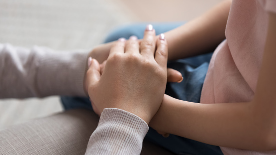 Mom giving support trust to little daughter holding hands, closeup 1134909210