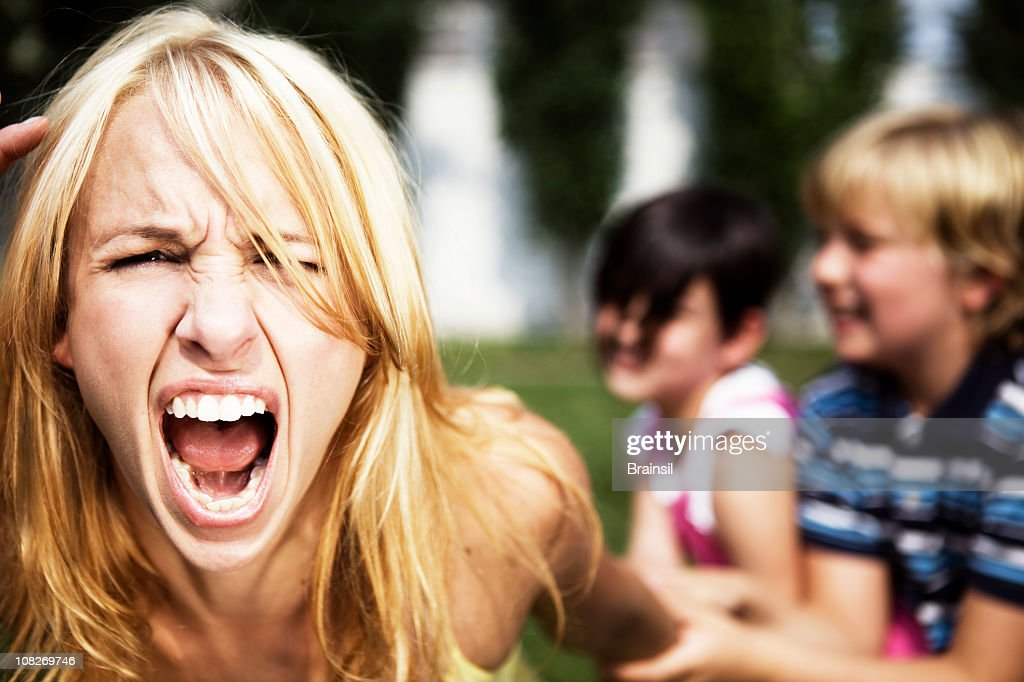 A mom going crazy while playing with her children : Stock Photo